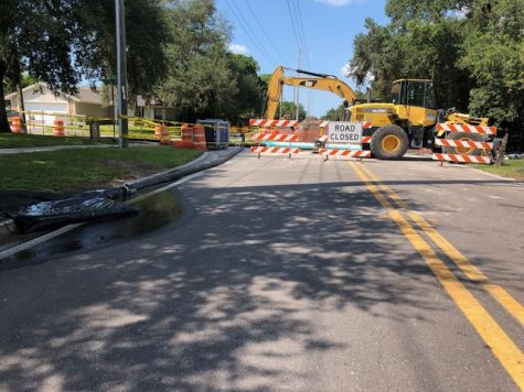19th St. is blocked with road closed signs, a pile of dirt, draining water, and a CAT excavator. Residents living off of this road face issues with driving to and from places.